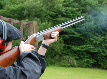 Man firing at clay pidgeon with rifle