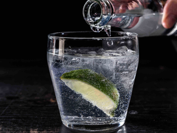 Glass of gin with tonic being poured in