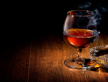 Glass of whiskey with cigar lit beside it