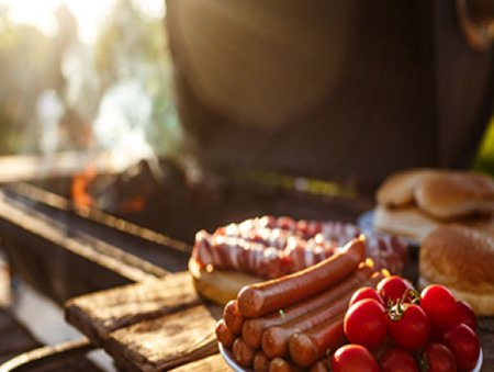 BBQ lit with Frankfurter sausages & cherry tomatoes waiting to be cooked