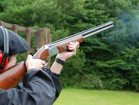 Man holding rifle shooting at clay pidgeons.