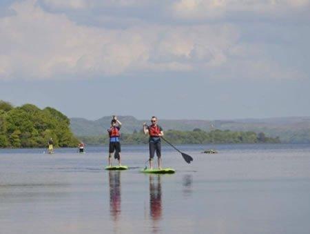 2 men doing stand up paddling on boards on lake in Sligo