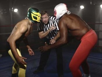 2 men about to wrestle with ref in between them