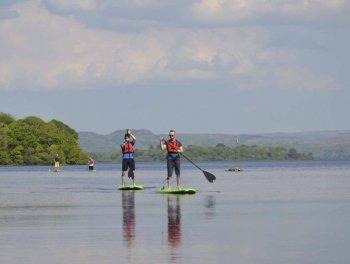 Man stand up paddling on lake
