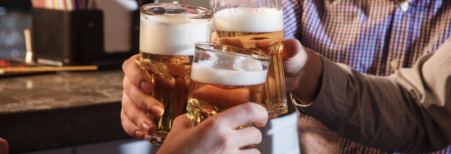 Men clinking beer glasses together